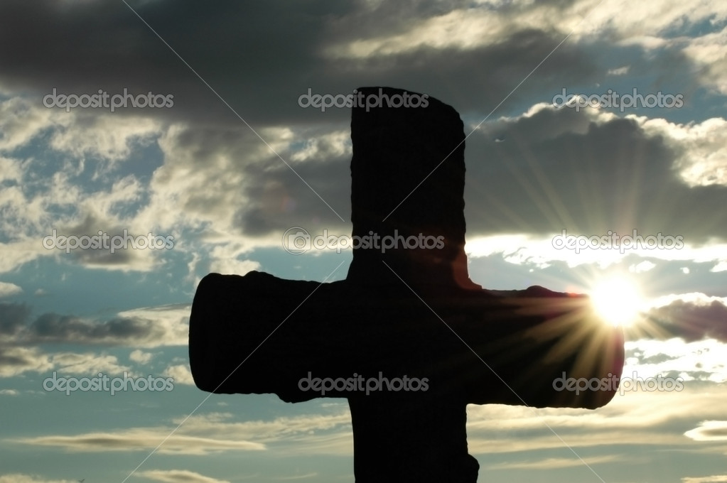 Silhouette of a cross against sun