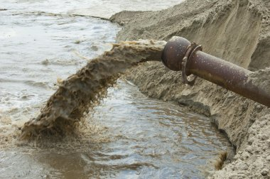 Dirty water flows from a pipe.