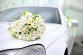 Svatební kytice leží na auto
