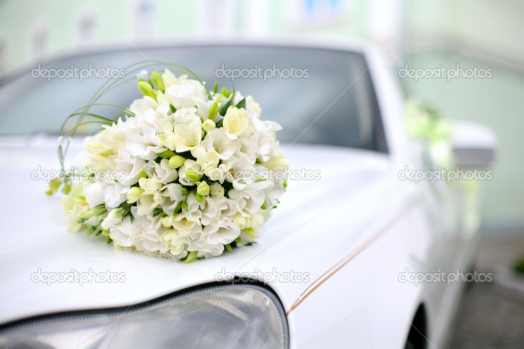 Wedding bouquet lies on the car