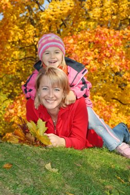 Mum with a daughter in autumn park
