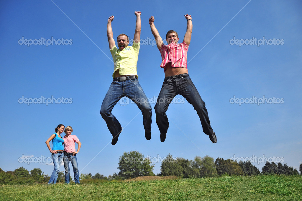Two guys are jumping with their hands up