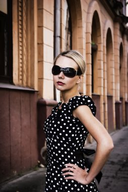 Beautiful girl in sunglasses on city str