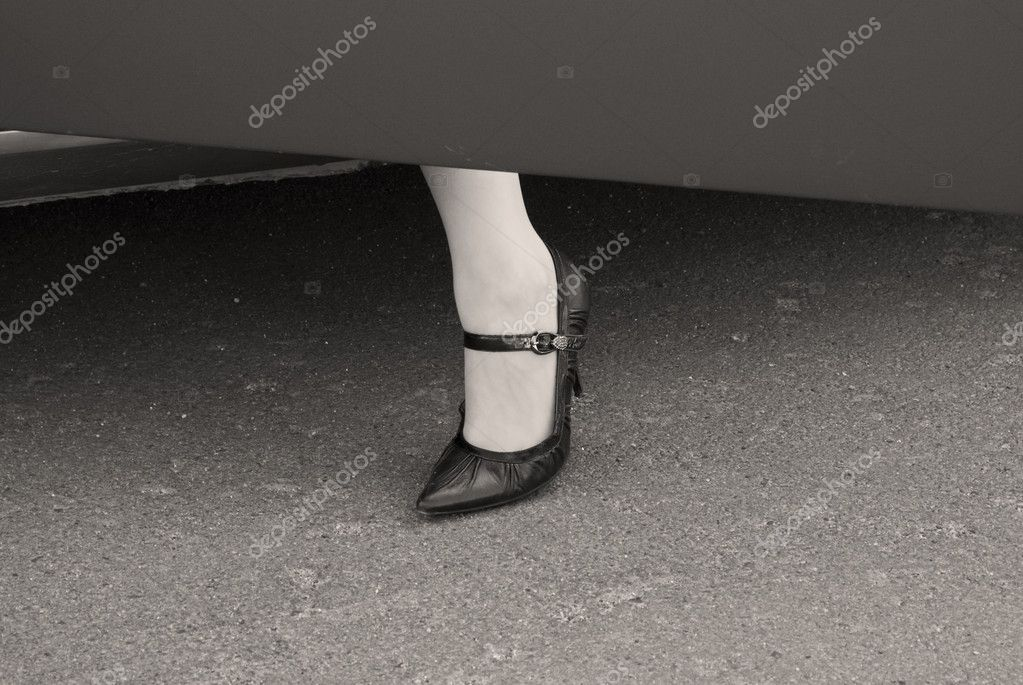 Female leg in a high heel shoe at a car door. Grayscale image