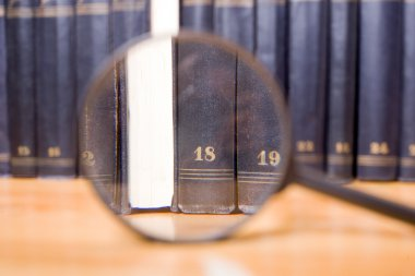 Close-up of magnifying glass with books