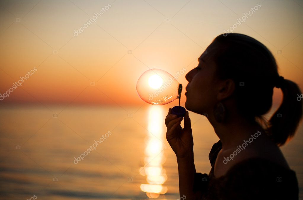Girl making soap bubbles over sunset