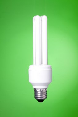 Energy saving lamp on green background