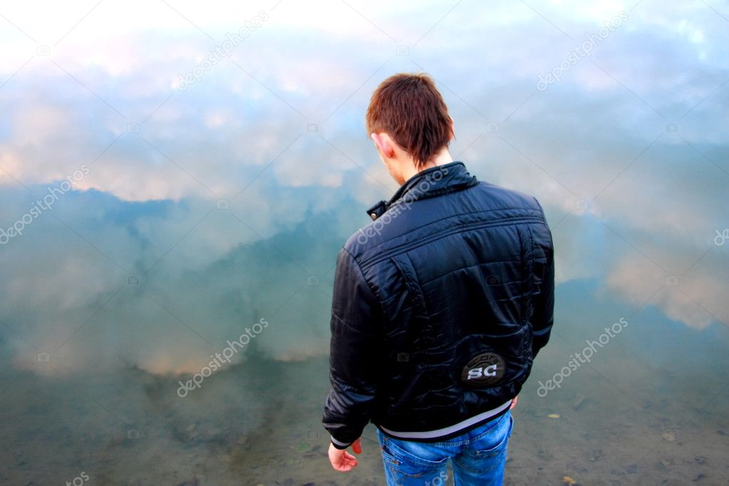 Young man in black jacket on the river