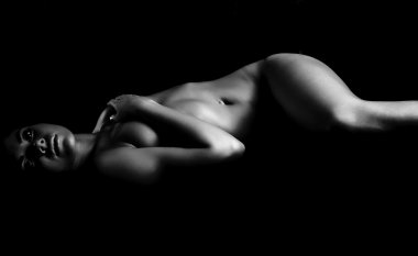 Dreaming naked girl in dark shadows