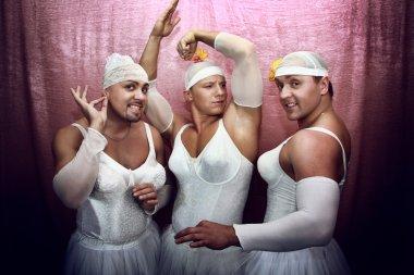 Three strong men in suits of ballerinas