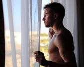 Fotografie Young attractive macho looking in window