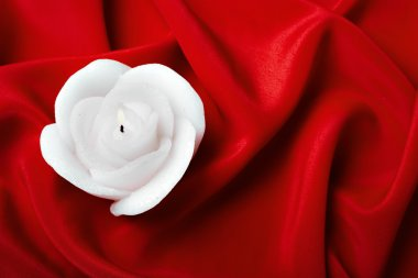 Candle as a rose against red silk