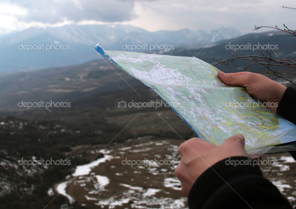 Map in hands against mountain view