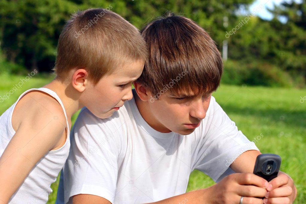 Adolescente Y El Nio Con El Telfono Mvil  Foto De -2328