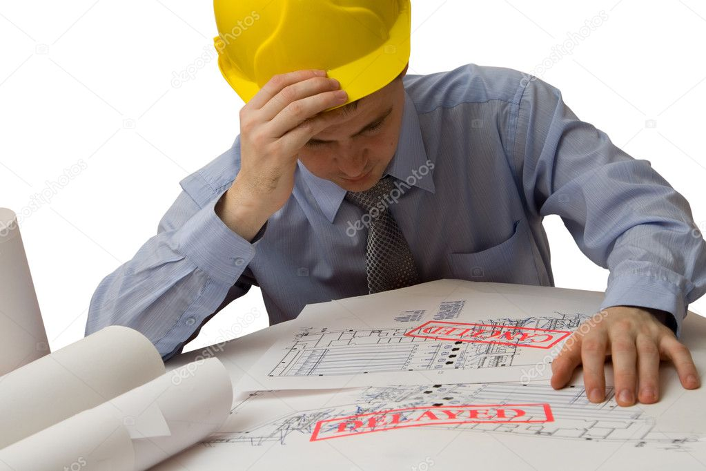 Sad architect is working with blueprints over white background
