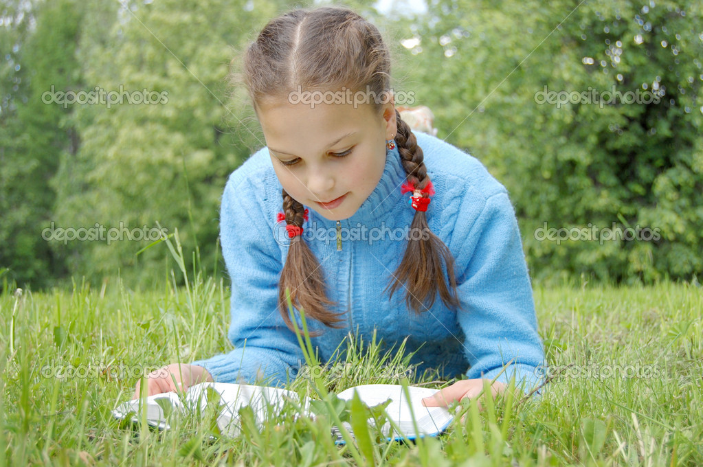 Young beautiful girl lays on green