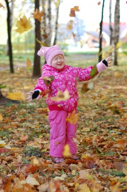 Little girl walks in autumn park