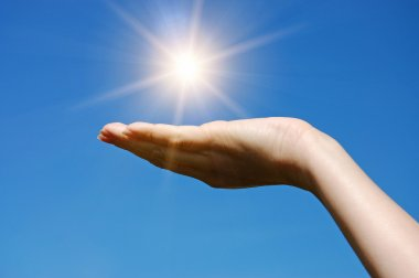 Female hand touching the Sun