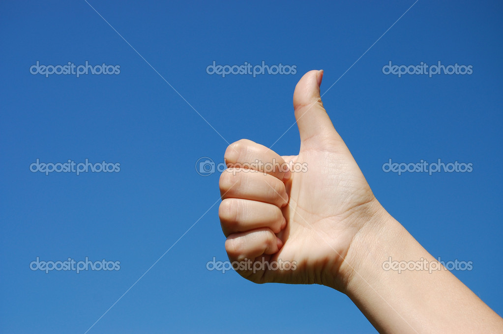 Thumbs up sign against blue sky