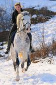 Fotografia ragazza sul cavallo bianco dressage in inverno