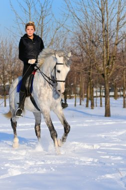 Girl on white dressage horse in winter