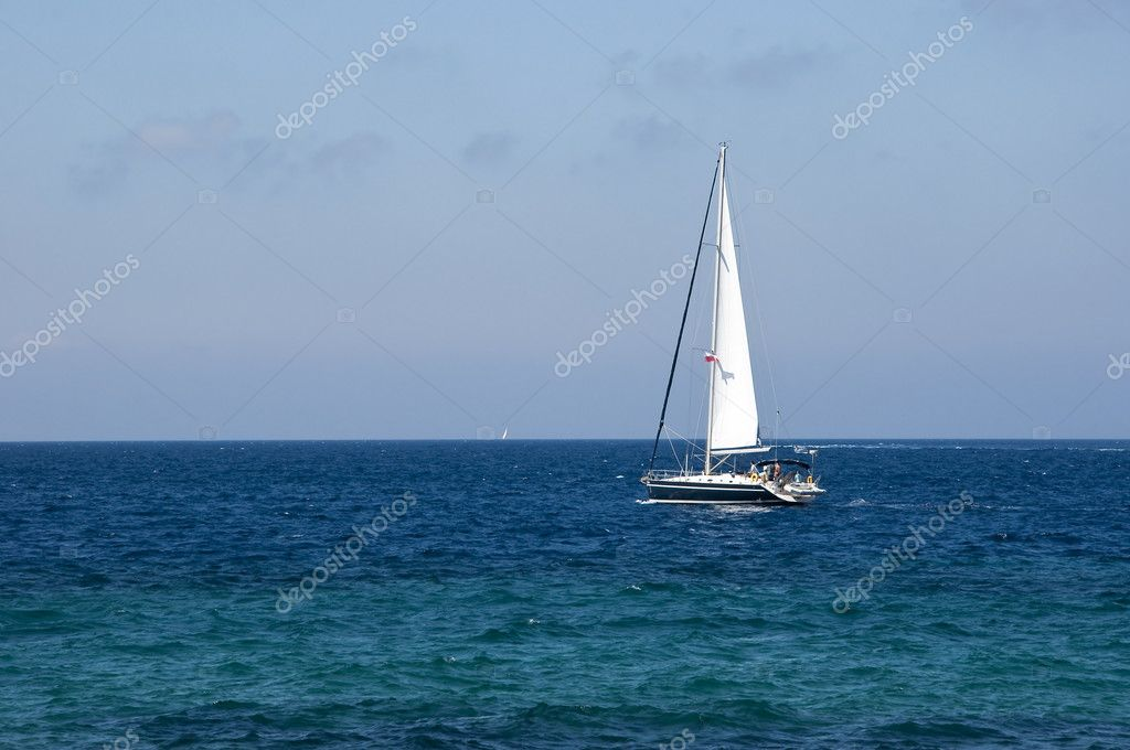 White sail on a yacht in the blue sea