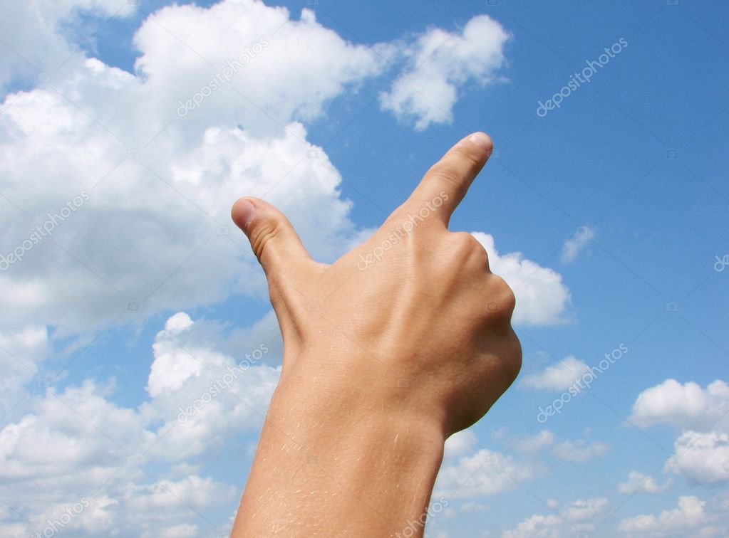 Hand gesture pointing against blue sky
