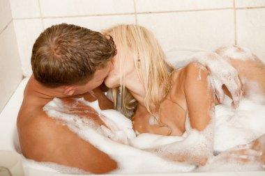 Couple kissing in bubble bath