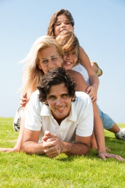 Family piled up on meadow enjoying