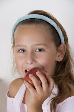 Young girl about to eat an apple