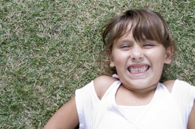 Young girl on grass with clenched teeth