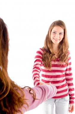 Friendly girls shaking hands and smiling