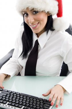 Young woman at work in christmas hat