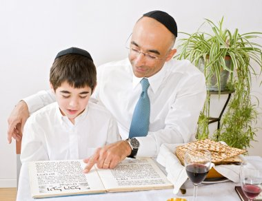 Father and son celebrating passover reading the Hagada stock vector