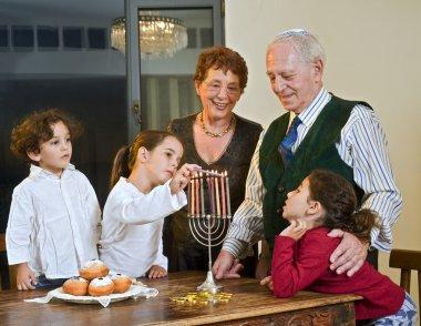 Grandperents and grandchildren lightening Hanukkiyah together stock vector