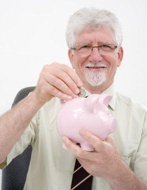 Senior man and piggybank
