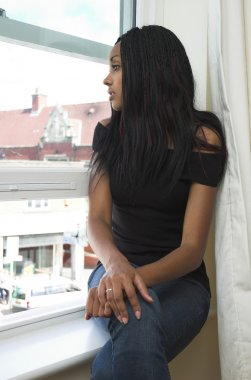 Casual girl relaxing at window.