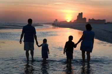 Young Family Silhouetted By Sunset