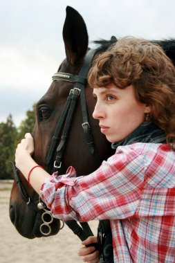 Young girl near horse looking ahead