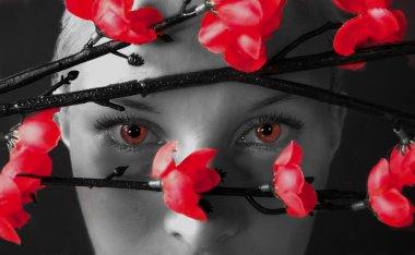 Girl watching through red bushes