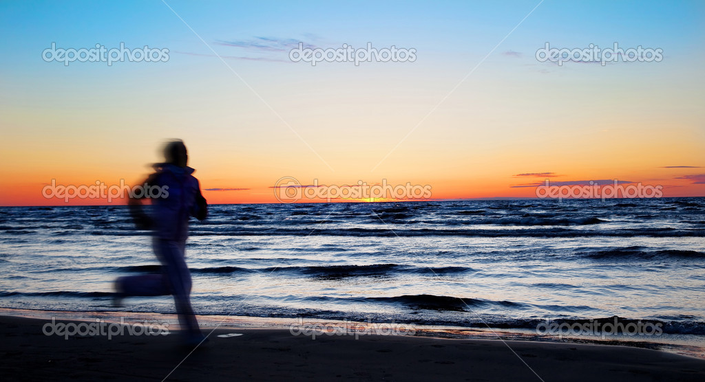 Young sportswoman running on the beach