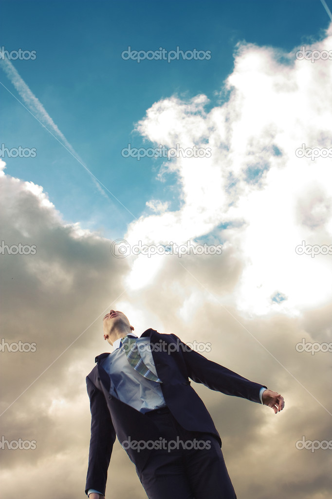 Young man in a suit against the sky