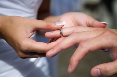 A bride giving her groom a ring