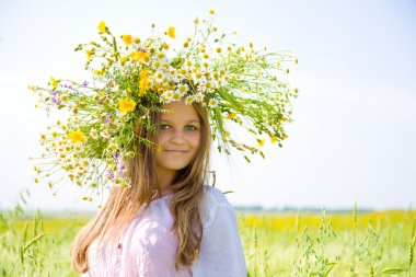 Young girl with chamomile wreath on head