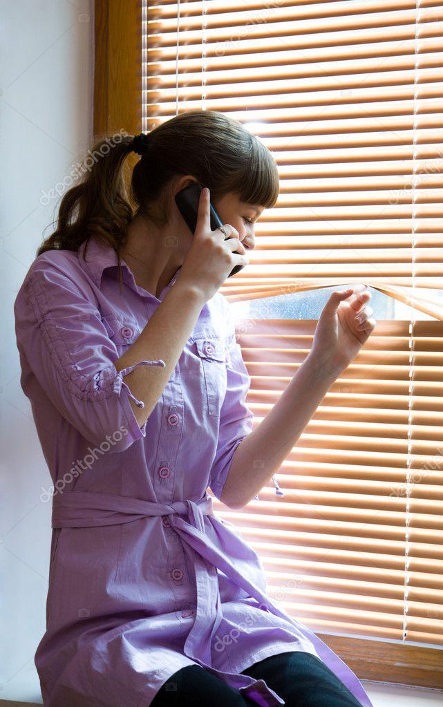 девушка разговаривает по телефону подсмотреть из окна