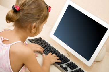 Little girl typing text at the computer