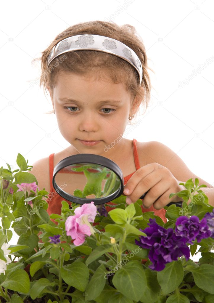 Child is looking through a magnifying gl