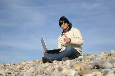 Casual man with laptop at the beach