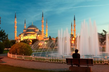 Man sitting on a bench near blue mosque