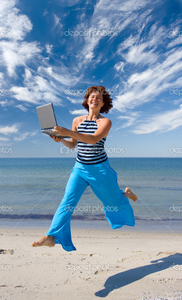 Smiling girl running with laptop